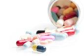 colored pills in laboratory near white container