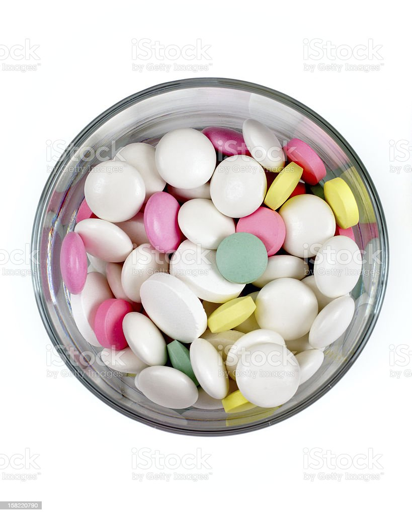 colored pills in  transparent glass on a white background, top royalty-free stock photo