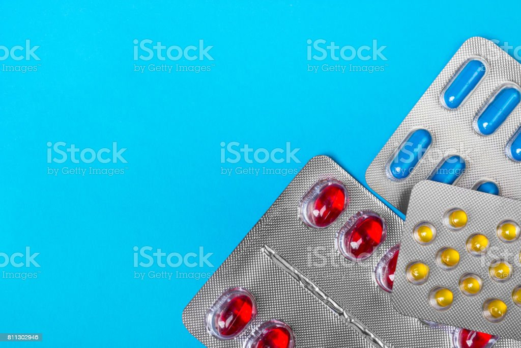 Colored pills, tablets and capsules on a blue background. Medicine and health. stock photo