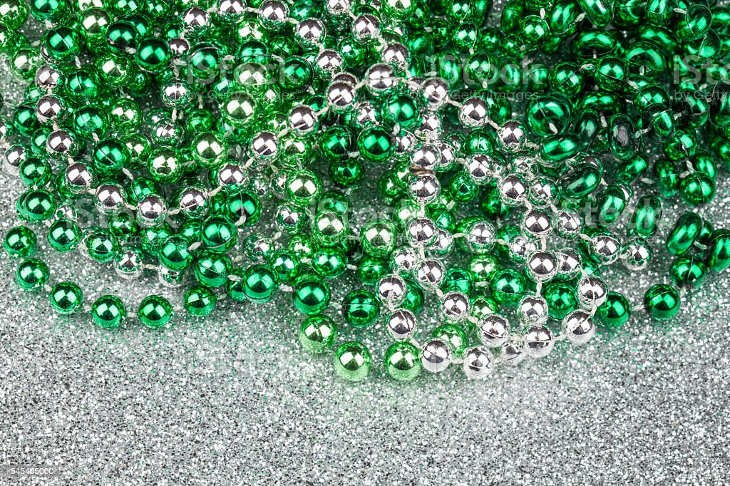 Colored plastic beads on silver glitter background stock photo