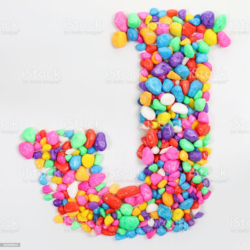 Colored stones arranged in a letter J. stock photo
