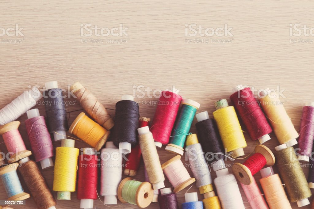 Colored thread spools on the wooden table. Sewing works. Handmade. Womanly hobby. stock photo