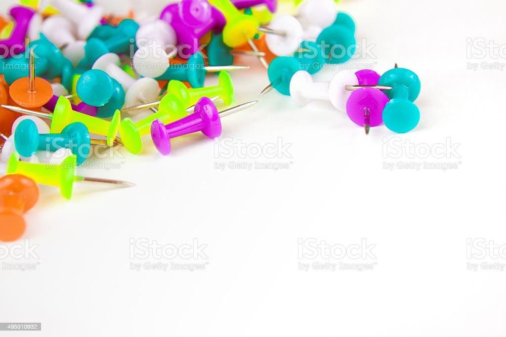 colored thumbtacks on a white background stock photo
