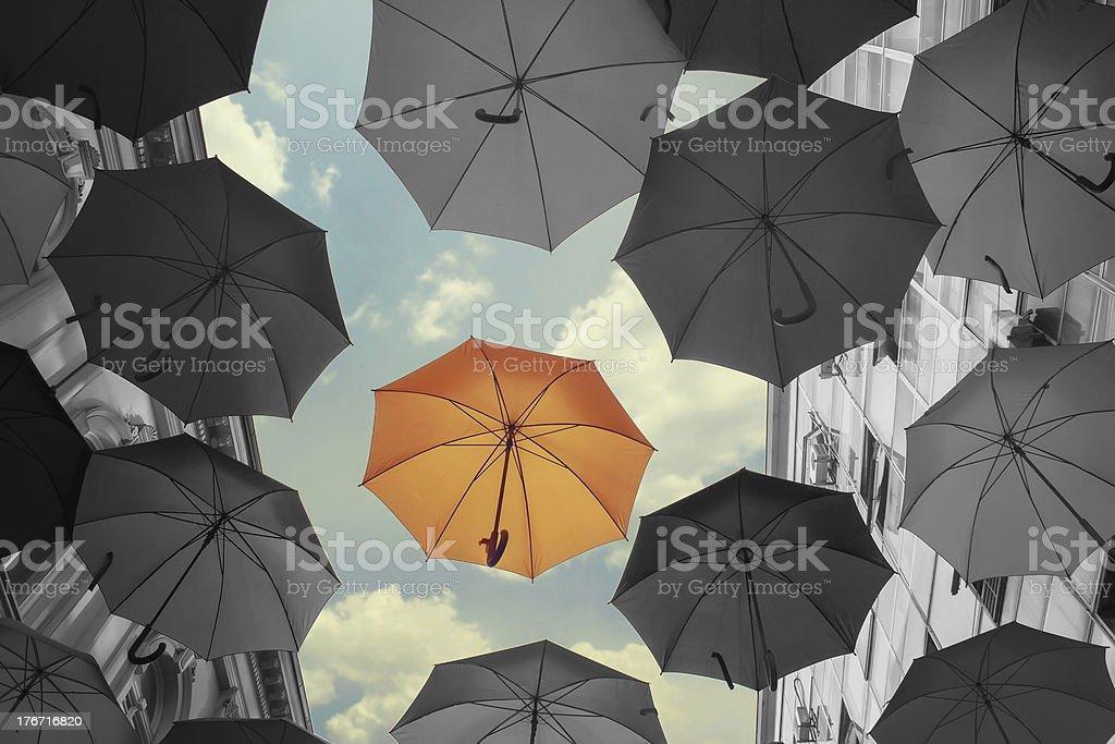 Colored umbrella surrounded by dark umbrellas stock photo