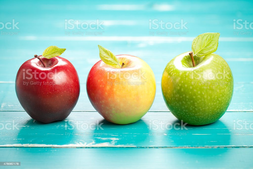 Colorful apples on turquoise table stock photo