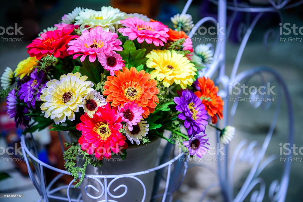 Colorful artificial flower bouquet decorated in basket stock photo