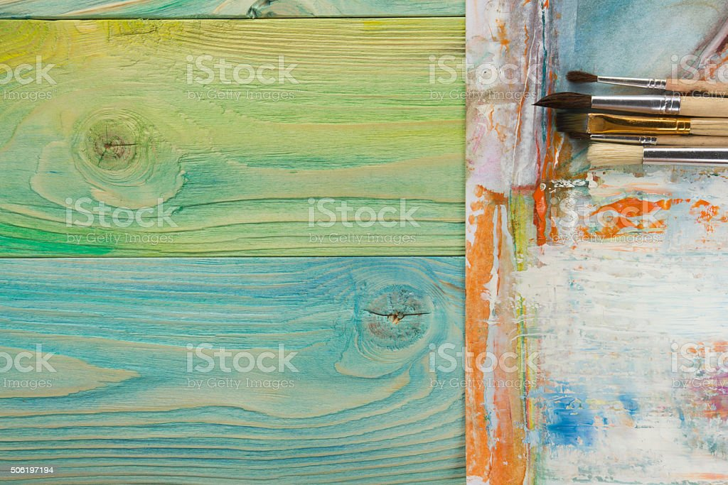 Colorful artistic paintbrushes, pencils on wooden deck table background stock photo