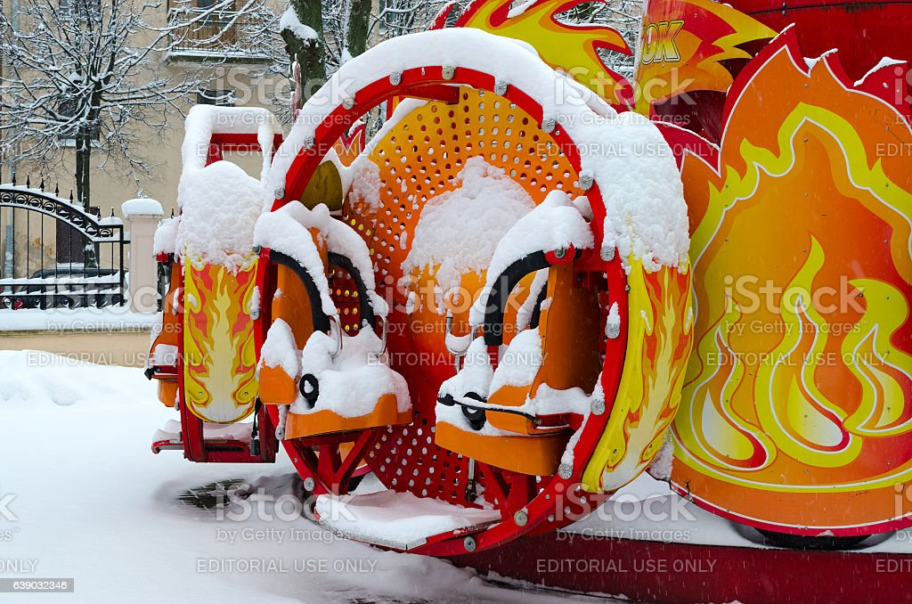 Colorful attraction covered by snow in winter park during snowfall stock photo