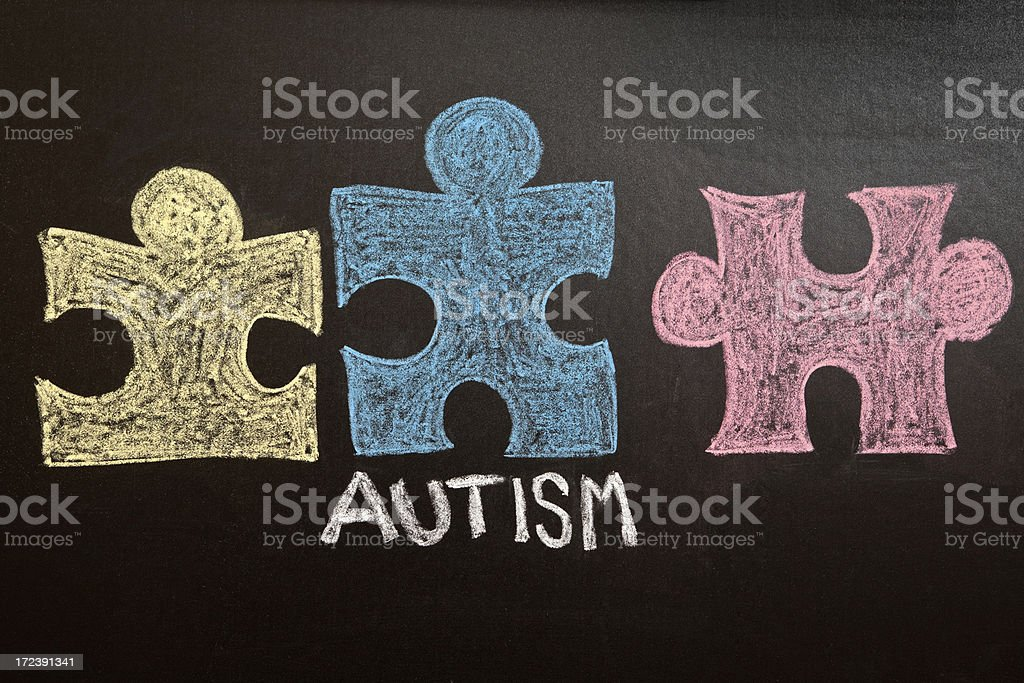 Colorful Autism Awareness Puzzle Pieces on Chalkboard stock photo