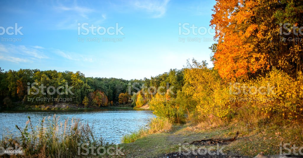 Colorful autumn landscape on a sunny day with trees with water and clouds stock photo