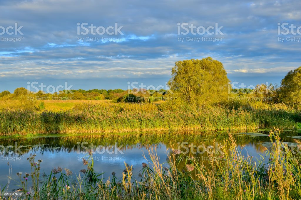 Colorful autumn landscape with a river and clouds stock photo