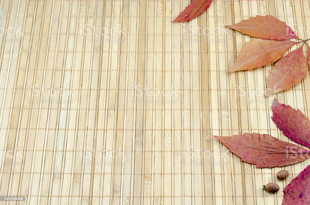 Colorful autumn leaves on a bamboo tablecloth royalty-free stock photo