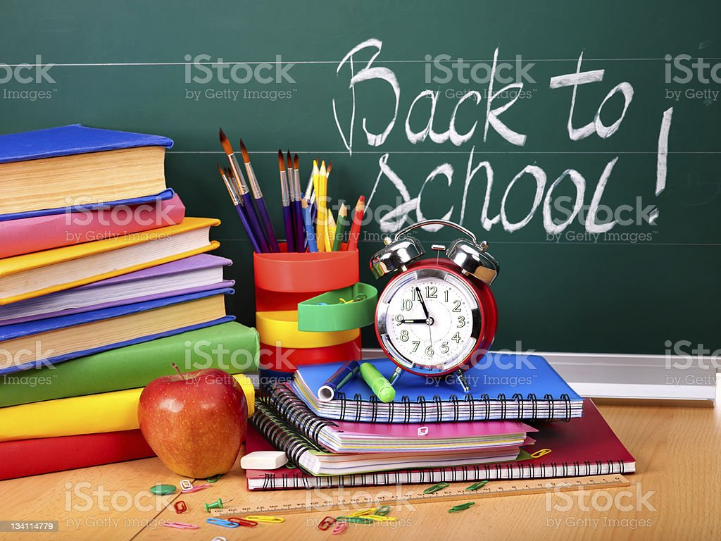 Colorful back to school supplies in front of a chalkboard stock photo
