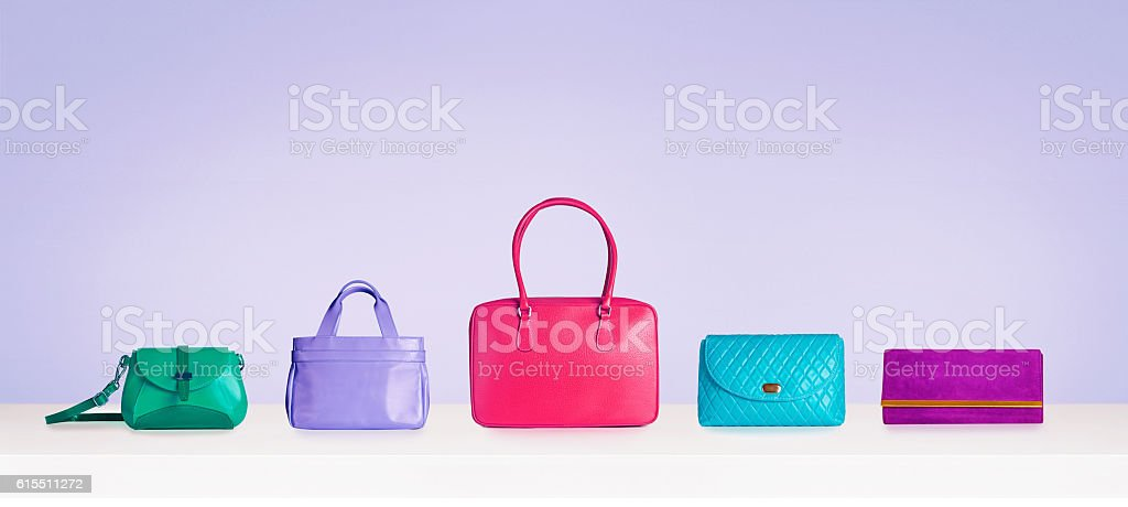 Colorful bags and purses isolated on purple background with copyspace. stock photo