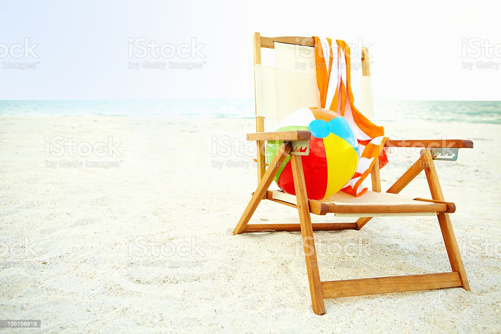 Colorful ball lying on a chair at the beach royalty-free stock photo