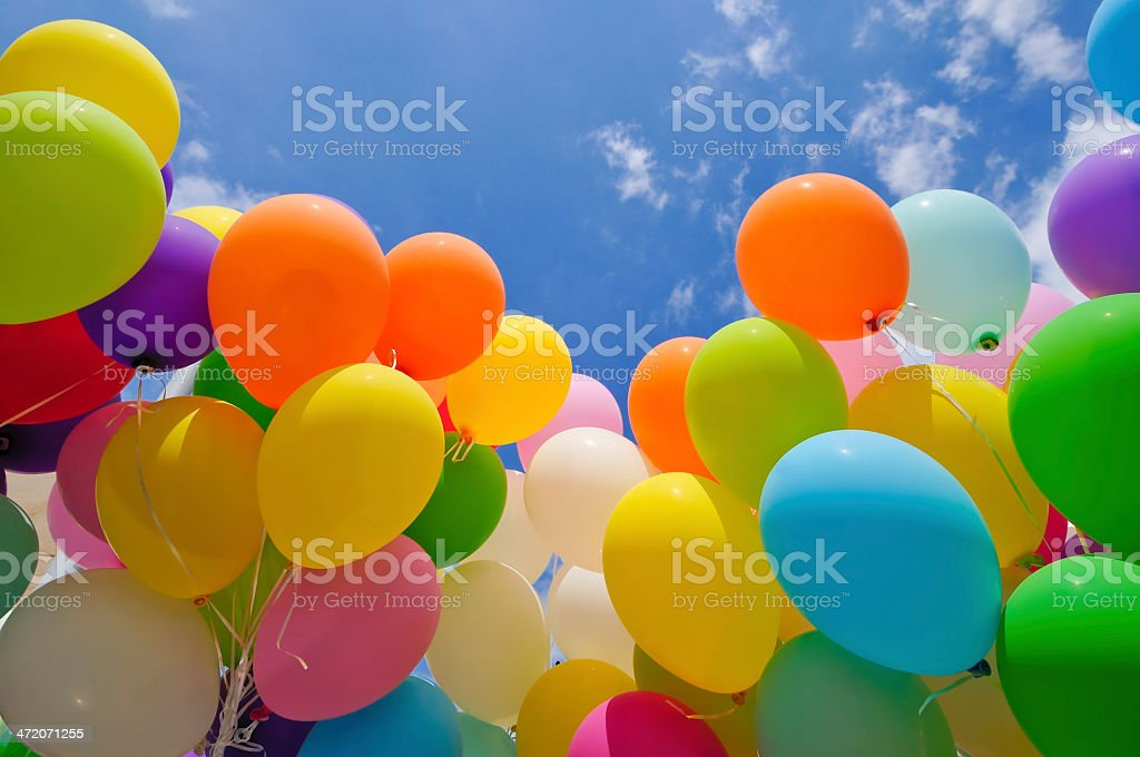 Colorful balloons in front of a blue sky stock photo