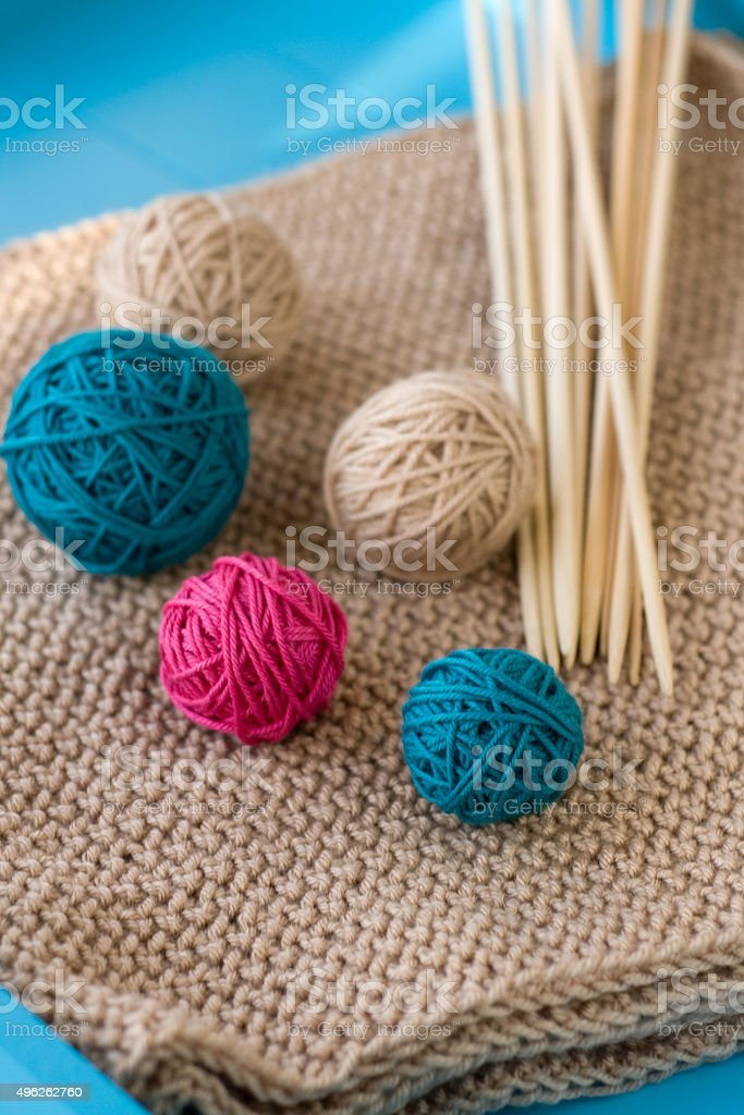 Colorful balls and wooden needles lying on beige stock photo