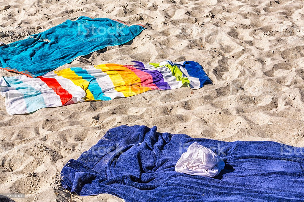 Colorful Bath Towels On Sandy Footprint Vacation Beach stock photo