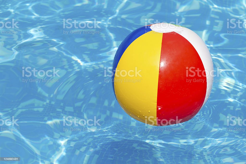 Colorful beach ball floating in a swimming pool royalty-free stock photo