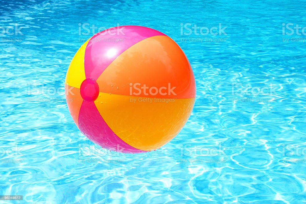 Colorful beach ball floating on clear blue water royalty-free stock photo