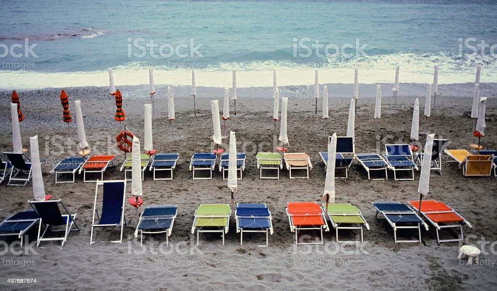Colorful beach - rows of Sun umbrellas and deck chairs stock photo