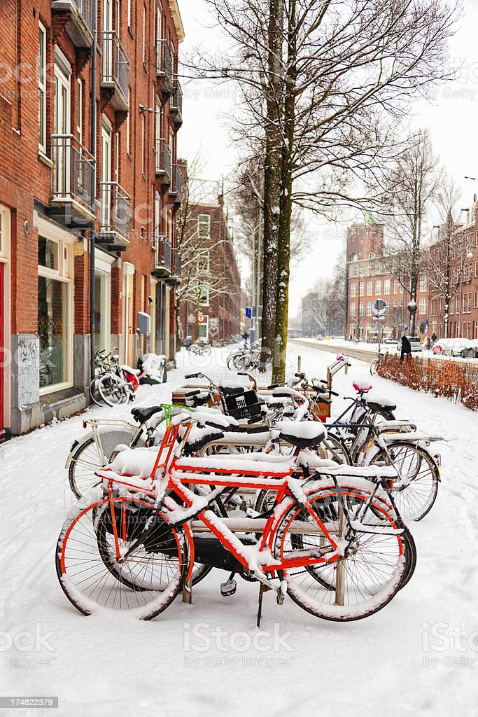 Colorful bicycles under white snow in Amsterdam royalty-free stock photo