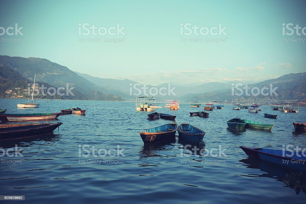 Colorful boats in Phewa Lake in Pokhara, Nepal stock photo