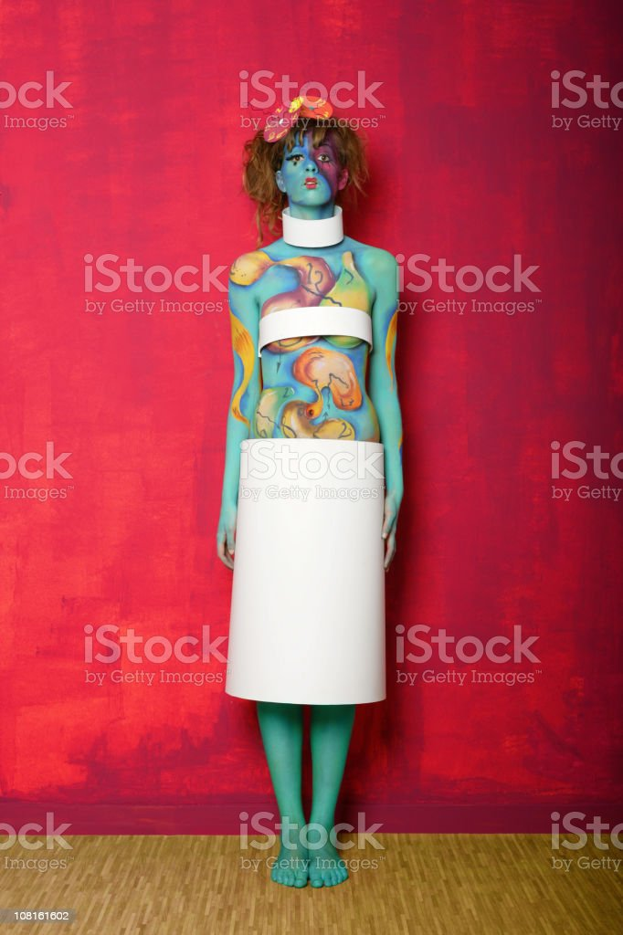 Colorful Body Painted Woman Posing Against Pink Wall royalty-free stock photo