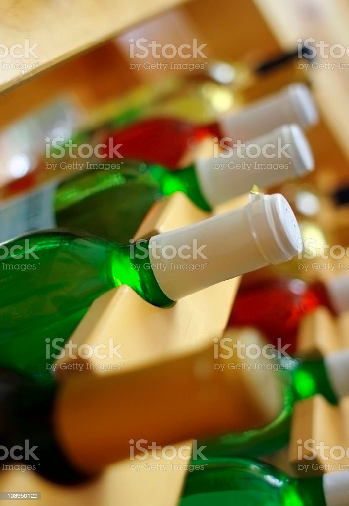 Colorful Bottles in a Natural Finish Wine Rack royalty-free stock photo