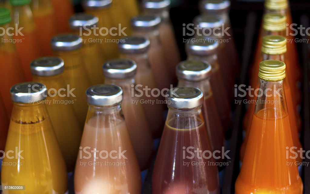 Colorful Bottles of Fruit Juice in Rows stock photo