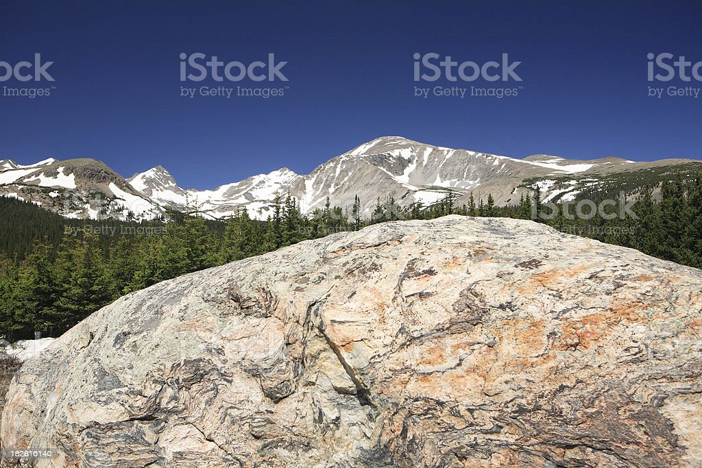colorful boulder with Rocky Mountains behind stock photo