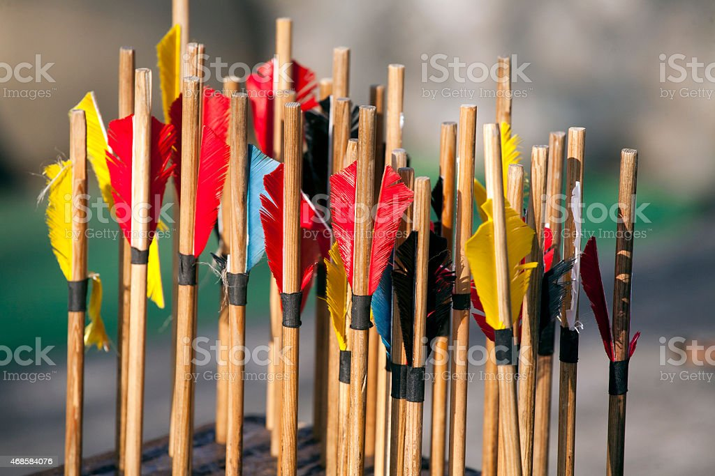 Colorful bow arrows closeup sticking in wood stock photo
