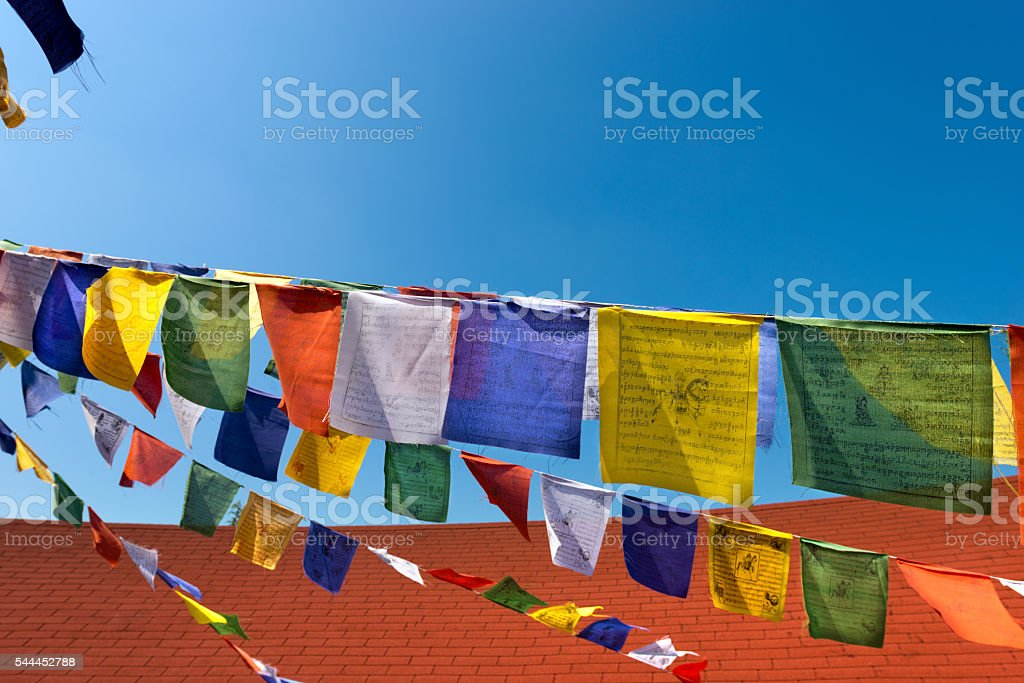 Colorful Buddhist Praying Flags on Blue Sky stock photo