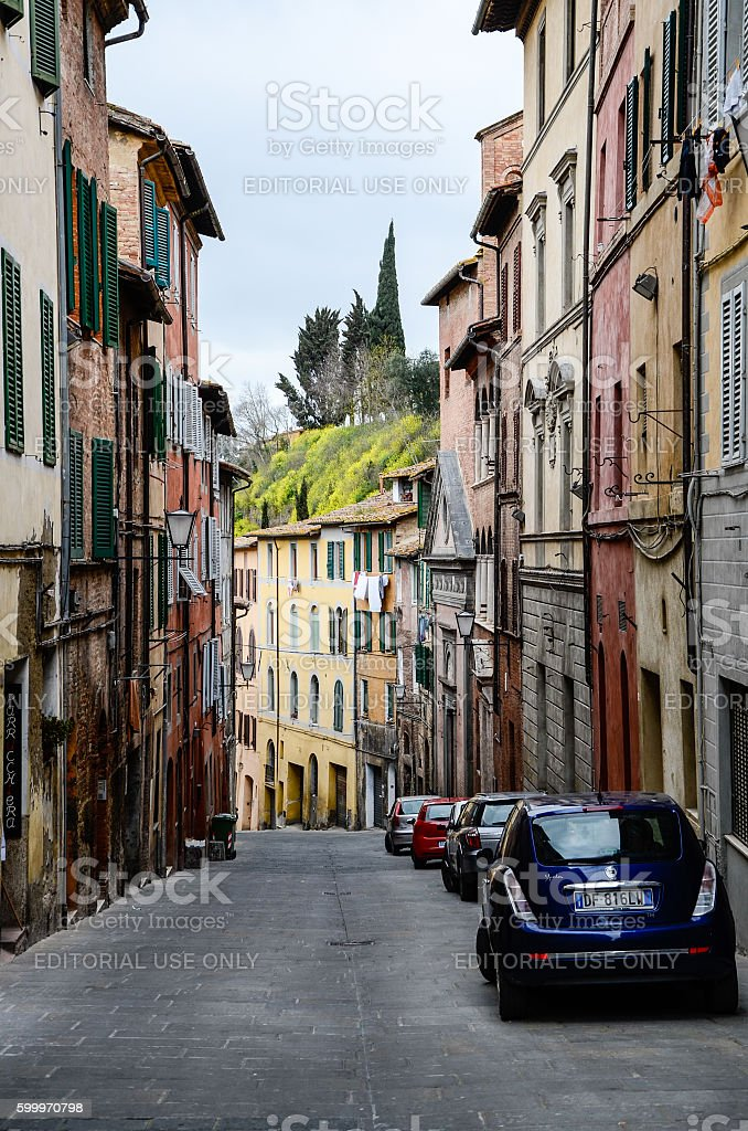 Colorful buildings on narrow street uphill, Siena stock photo