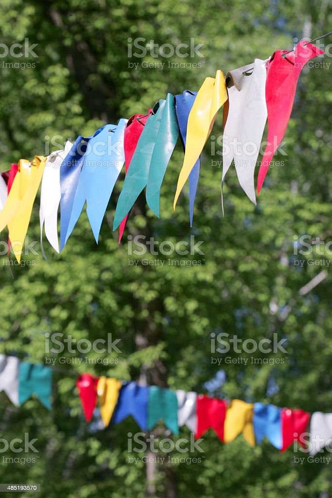 colorful bunting flags against green forest stock photo
