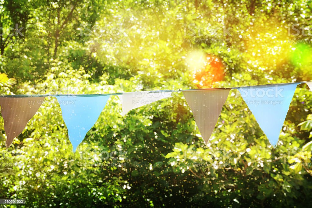 Colorful bunting flags against green trees stock photo