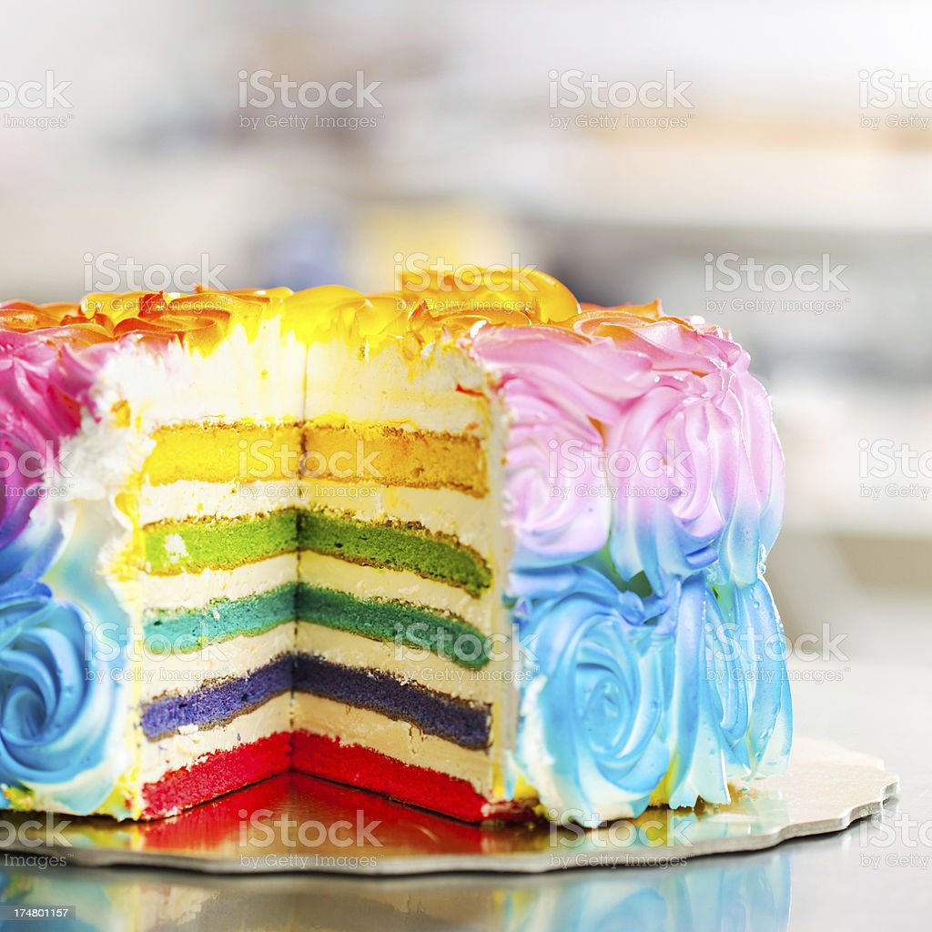 Colorful cake with iced roses covering it and white icing stock photo