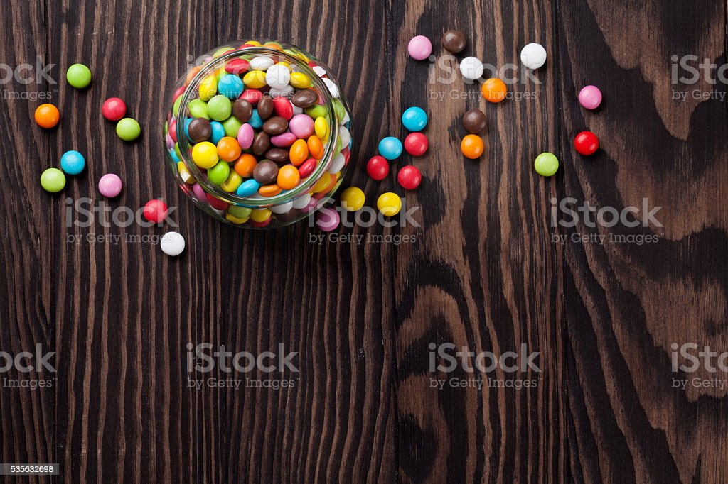 Colorful candies on wooden table stock photo