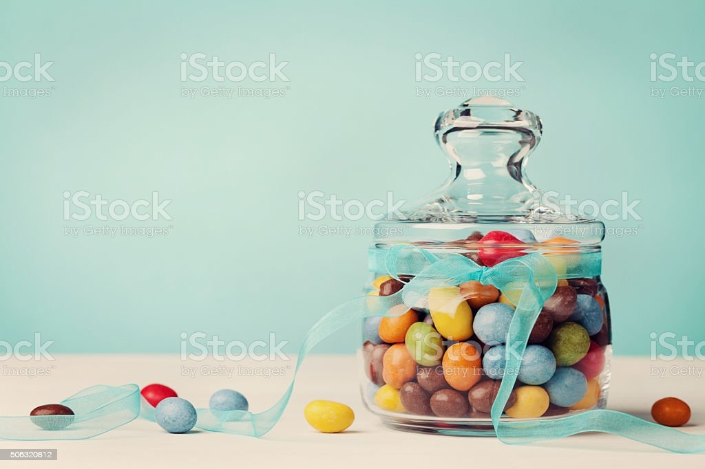 Colorful candy jar decorated with bow ribbon, gifts for Birthday stock photo