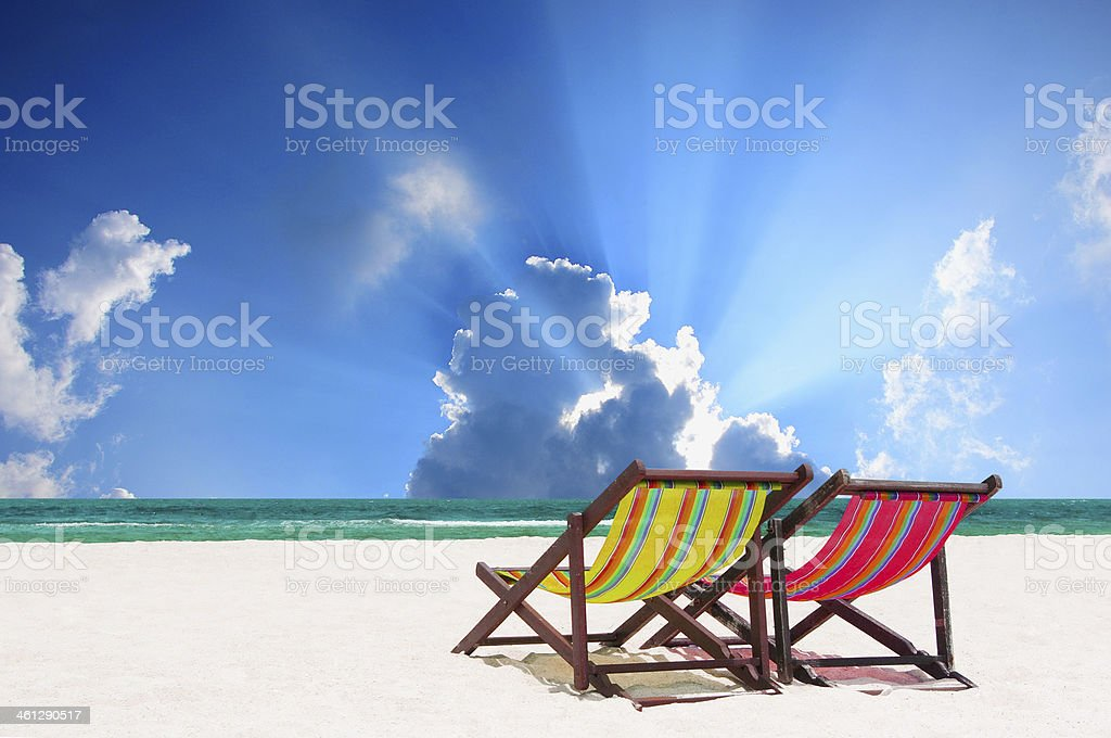 Colorful canvas beach loungers overlooking calm sea royalty-free stock photo
