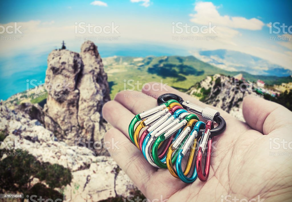 colorful carabiner climbing on a palm stock photo