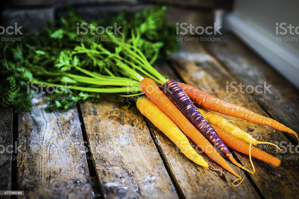Colorful carrots on rustic wooden background stock photo