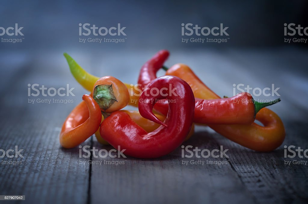 Colorful chili peppers on old wooden background stock photo
