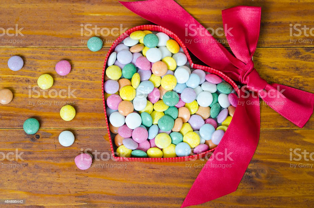 Colorful chocolate pills in a heart shaped box royalty-free stock photo