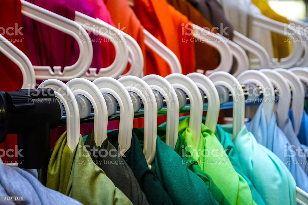 Colorful clothes on hangers stock photo