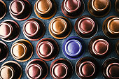 Colorful coffee capsules on the dark table top view