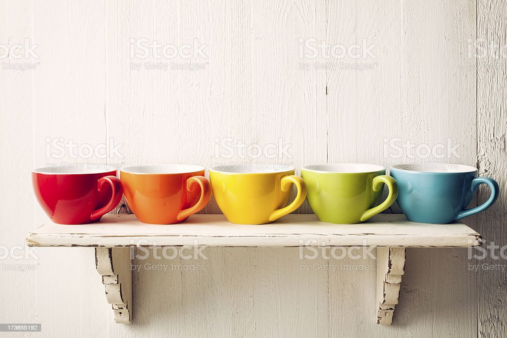 Colorful coffee cups on shabby shelf stock photo