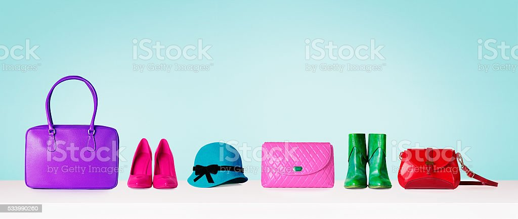Colorful collections of bags and purses. Isolated on blue. stock photo