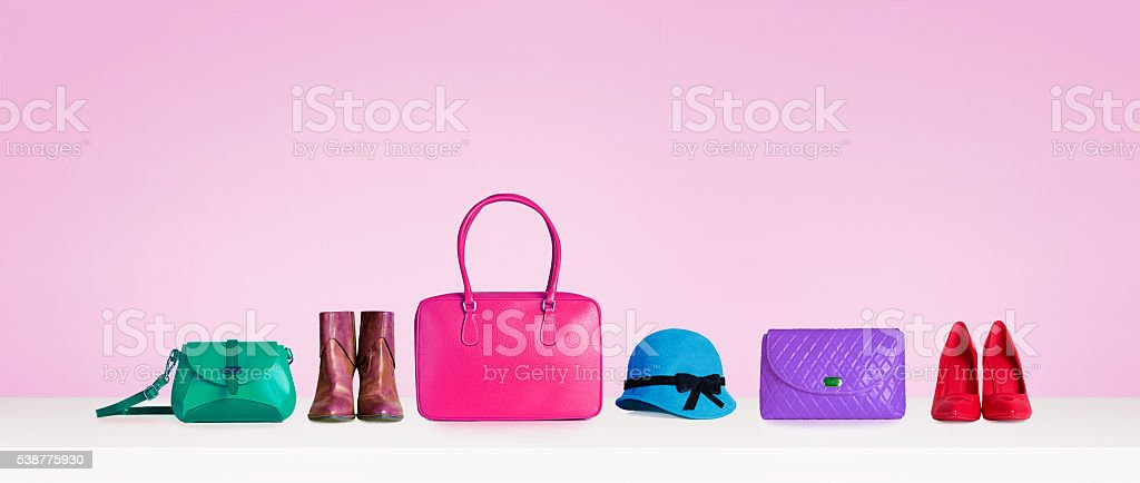 Colorful collections of bags and purses. Isolated on pink. stock photo