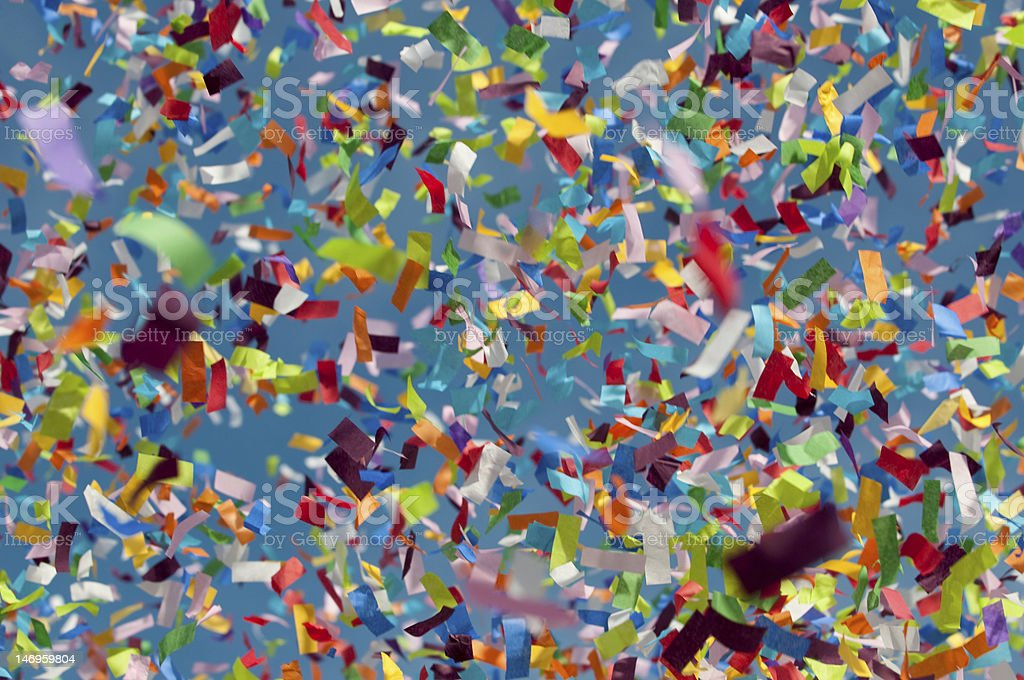 Colorful confetti in foreground with blue sky behind stock photo